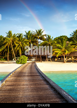 Pont en bois à island beach resort, belle arc-en-ciel de couleur vert frais sur palmiers, hôtel de luxe sur l'île Banque D'Images