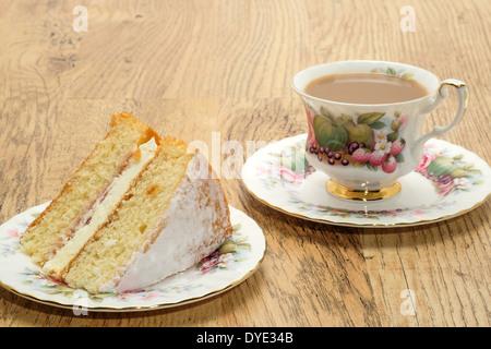 Une tranche de gâteau éponge Victoria avec une boisson chaude servie dans une tasse et soucoupe en porcelaine Banque D'Images
