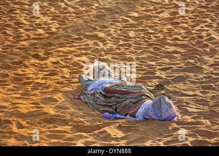 Man sleeping on sand Banque D'Images