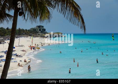 Coconut palm tree et Xanadu mansion à plage de sable blanc de Varadero Resort Cuba avec les touristes dans l'eau Banque D'Images