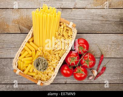Divers les pâtes, les tomates et les épices sur fond de table en bois Banque D'Images