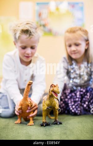 Enfants jouant avec des Dinosaures jouets en maternelle Banque D'Images