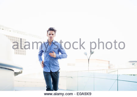 Mid adult man fonctionnant en bas du parking sur le toit Banque D'Images