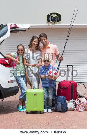 Portrait of smiling family voiture d'emballage à sunny driveway Banque D'Images