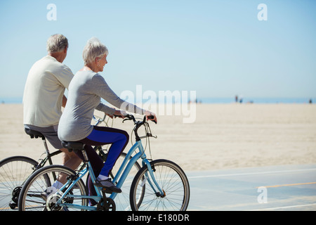 Senior couple riding bicycles on beach Banque D'Images