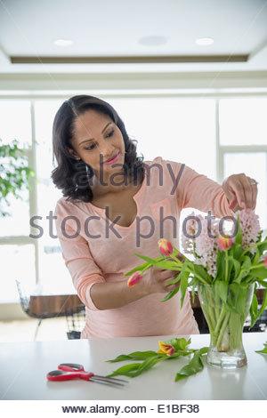 Pregnant woman arranging flowers Banque D'Images