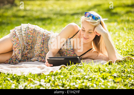 Young woman lying in forest looking at digital tablet Banque D'Images