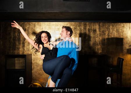 Jeune homme danse et exerçant son jeune femme en discothèque Banque D'Images