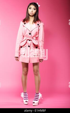 Jeune femme d'origine asiatique Fashion model en manteau rose standing in Studio Banque D'Images