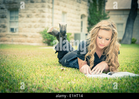 Portrait of young woman lying on grass reading a book Banque D'Images