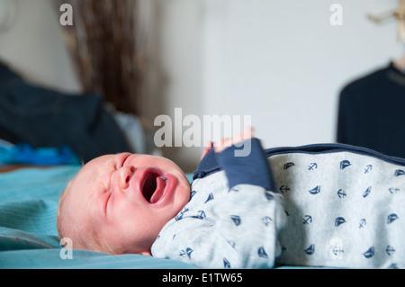 Bébé qui pleure sur une douce couverture en armes déménagement Banque D'Images