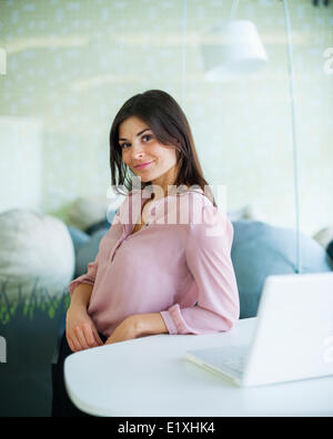 Portrait of young woman smiling at table Banque D'Images