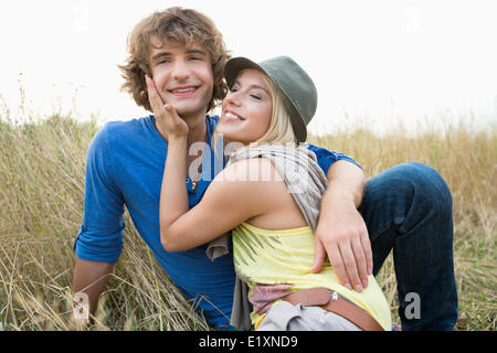 Happy loving couple relaxing in field Banque D'Images