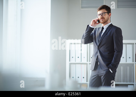 Handsome businessman en costume et lunettes parlant sur l'phone in office Banque D'Images