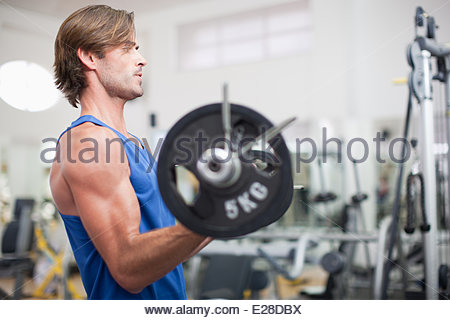 Man lifting barbell in gymnasium Banque D'Images