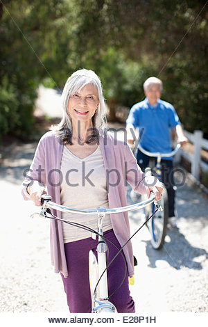 Smiling older couple riding bicycles Banque D'Images