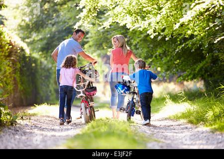 Poussant la famille de vélos le long de la voie de Pays Banque D'Images