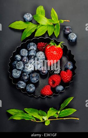 Les baies fraîches sur fond sombre. Fraises, framboises et bleuets. La santé, l'alimentation, le jardinage, le concept Banque D'Images