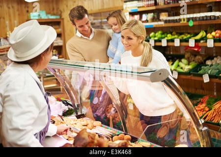 Female Sales Assistant au service de traiteur en famille Banque D'Images