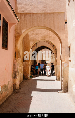 Les gens marchent dans les rues étroites avec de grands murs en argile adobe rose dans la médina, Marrakech, Maroc Banque D'Images