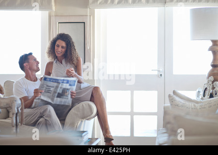 Couple reading newspaper in salon Banque D'Images