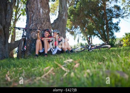 Les cyclistes se reposant par tree Banque D'Images