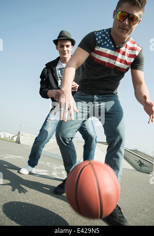 Les jeunes hommes jouant au basket-ball en skatepark Banque D'Images