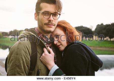 Couple standing in park par river Banque D'Images