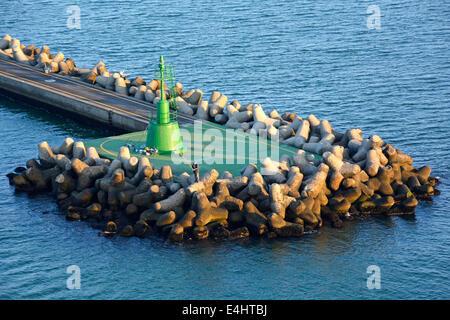Dolosse les blocs de béton dans les défenses de la mer pour protéger le canal vert à l'entrée du canal de marqueur Banque D'Images