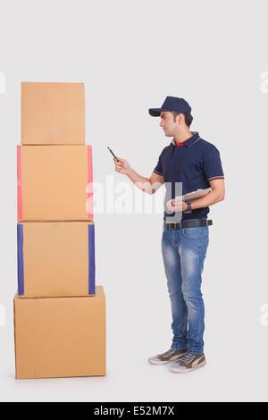 La longueur totale de l'homme comptant livraison de boîtes de carton à l'arrière-plan blanc Banque D'Images
