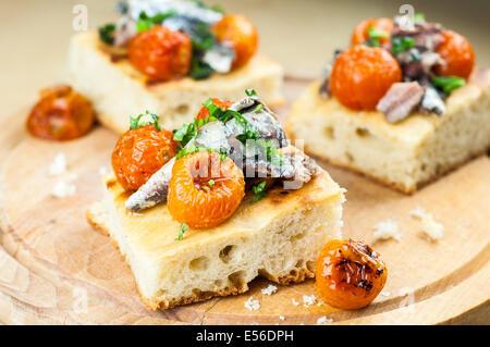 Délicieux avec de la focaccia de sardines et tomates cerises sur bois Banque D'Images