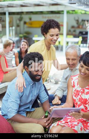 Des amis à l'aide de digital tablet at party Banque D'Images