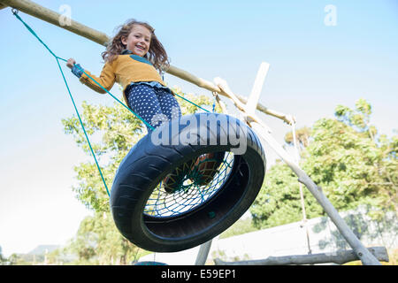 Girl playing on tire swing Banque D'Images