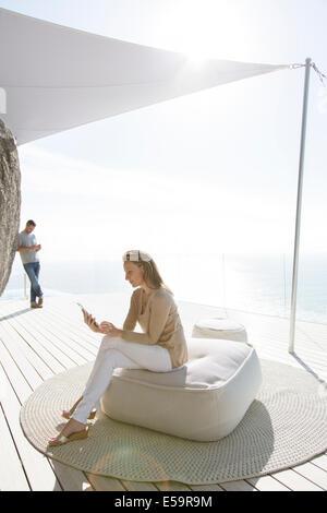 Woman using digital tablet sur balcon moderne Banque D'Images