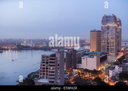Au crépuscule du Nil au Caire, Égypte - avec le Fairmont Nile City Hotel immeuble sur le front de mer Banque D'Images