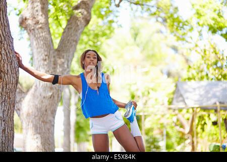 Jeune coureuse de préchauffage dans park Banque D'Images