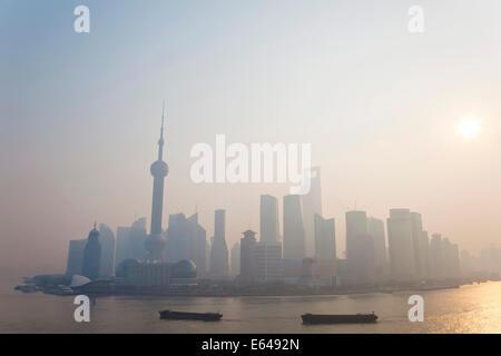Lever de soleil sur l'horizon de Pudong et de barges sur la rivière Huangpu, Shanghai, Chine Banque D'Images