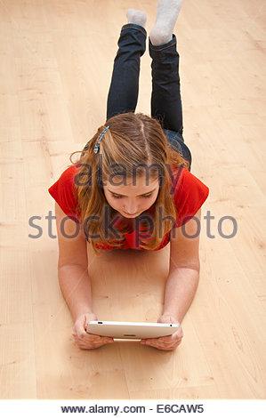 Girl 10 ou 11 ans, la lecture sur une tablette Banque D'Images