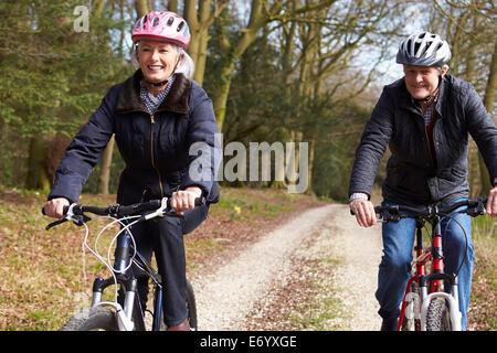 Couple à vélo le long de la rue urbaine ensemble Banque D'Images