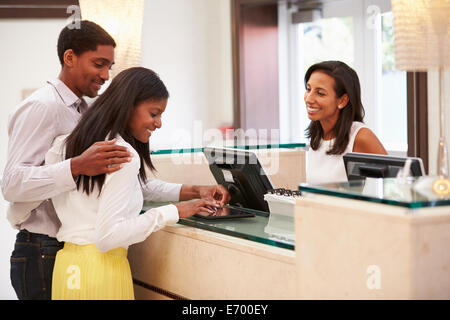 Couple de l'enregistrement à la réception de l'hôtel Using Digital Tablet Banque D'Images
