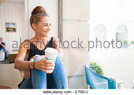 Mid adult woman sitting on window ledge de boire du café, à la fenêtre de Banque D'Images
