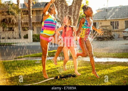 Trois jeunes filles courir et sauter en jardin réseau sprinkleur Banque D'Images