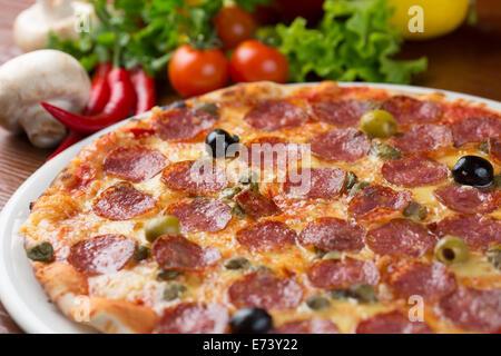 Salami italien pizza sur la table avec des légumes Banque D'Images