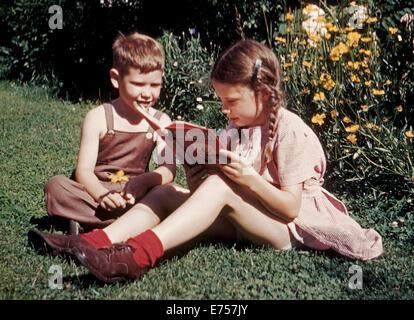 En 1945, un jeune frère et soeur ont été photographiés au début de film couleur Kodachrome en lisant un livre sur Banque D'Images