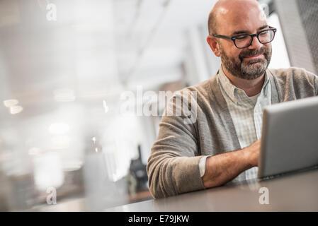 La vie de bureau. Un homme assis à une table, en train de travailler sur un ordinateur portable. Banque D'Images