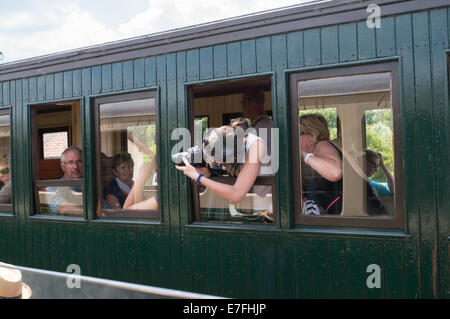 Young woman taking photograph hors de la fenêtre du train, Chemin de Fer de la Baie de Somme, France, Europe Banque D'Images