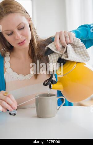 Jeune femme faire du thé Banque D'Images
