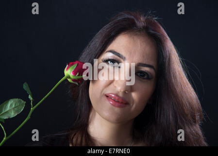 Belle brune femme tenant une rose rouge Banque D'Images
