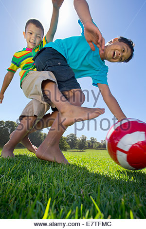 Smiling boys playing soccer in park Banque D'Images
