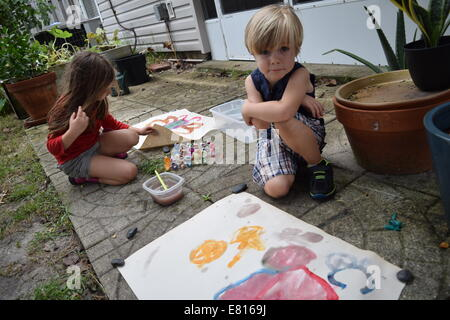 Boy and girl making art in backyard Banque D'Images